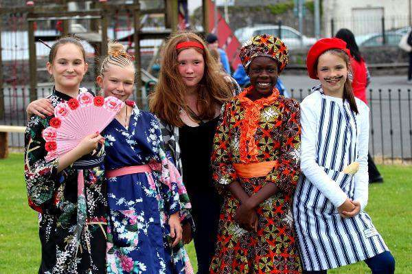 Group of children from diverse cultures pictured at a food festival celebrating multiculturalism.